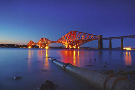 polution: The Forth Rail Bridge crossing between Fife and Edinburgh, Scotland. Rusty iron pipe disappearing in the water. Night scene