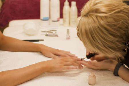 Varnishing nails in beauty salon photo