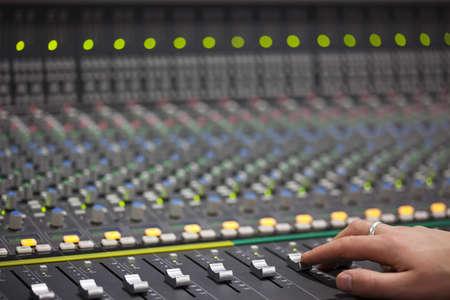 Someone is sliding Large Music Mixer's slider in recotding studio. Closeup