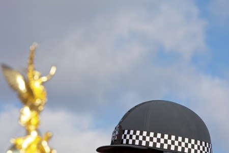 riding helmet: La polic�a brit�nica checkered montar el casco con el cielo y la escultura de oro en el fondo