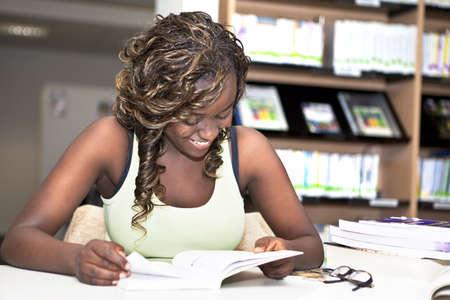 adolescentes estudiando: Bastante adolescente negro africano chica estudiante universitario sonriendo y leyendo un libro en la biblioteca Foto de archivo