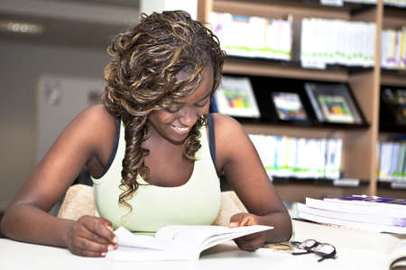 Nätt tonårs- svart afrikansk högskolestudent flicka leende och läsa en bok i biblioteket