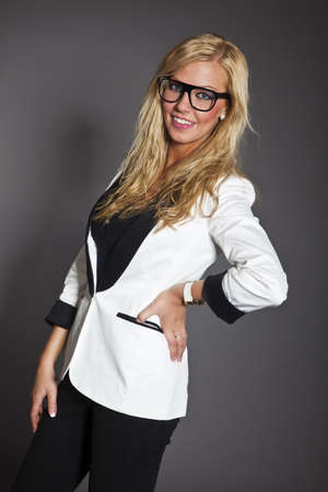 studio shot portrait of a young blond long hair caucasian business woman in smart outfit wearing glasses photo