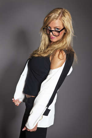 studio shot portrait of a young blond caucasian business woman in smart outfit wearing glasses photo