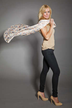 portrait of a young blond slim caucasian woman holdin flying silk scarf  studio shot on gray background photo