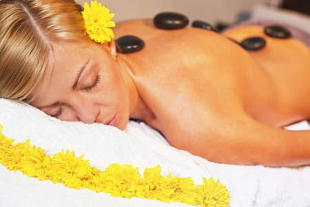 Beautiful young woman getting a stone massage in spa salon Stock Photo - 14461020