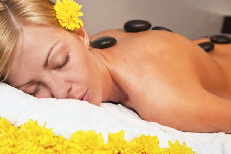 Beautiful young blond woman getting a stone massage in spa salon photo