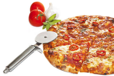 Close-up of stone backed pizza margarita with sun dryed tomatos and pesto with disk pizza knife.  isolated on white background