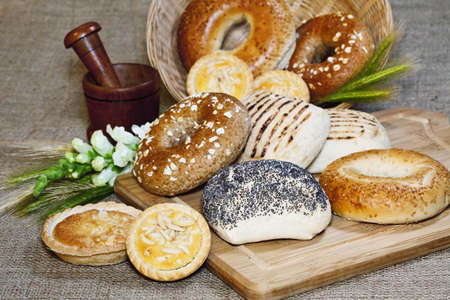 Various baked goods with a cutting board, mortar and cereal ears Stock Photo - 14627225