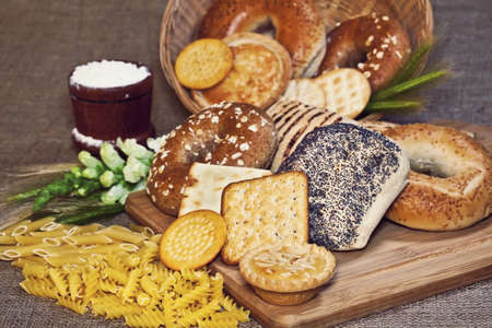 Various baked goods with a cutting board, mortar with flour, pasta and cereal ears  Stock Photo - 14627213