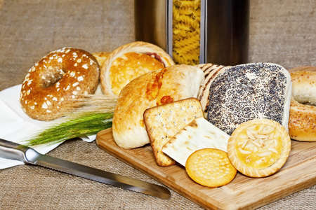 Vaus baked goods with a cutting board, bread knife, jar with pasta and cereal ears  Stock Photo - 14627222