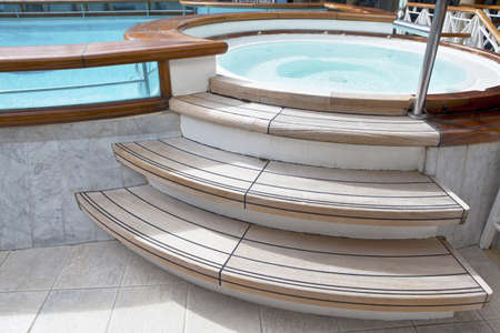 Whirlpool jacuzzi with wooden steps and pool on the deck of a cruise ship  Stock Photo