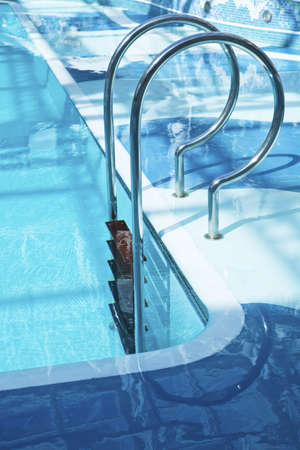 Curved chrome ladder leading into the turquoise water of a pool photo