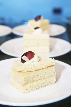 Row of small sponge-cakes on plates. Restaurant lunch buffet display photo