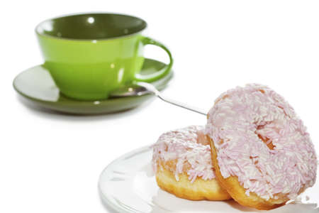 Closeup of iced and sprinkled doughnuts on plate with tea or coffee cup on background isolated on white  Slective focus on foreground photo