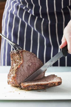 Närbild av grillat kött blir huggen av en kock