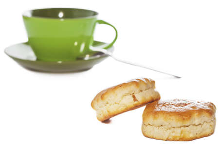 buttery: Closeup of two buttery scones with tea cup on background isolated on white  Selective focus on foreground Stock Photo