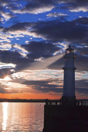 Lighthouse at astonishing sunset on vibrant sky background with light beam  Edinburgh, Scotland photo