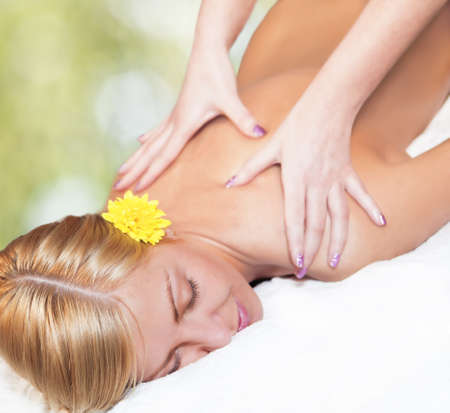 Young blond caucasian woman receiving back massage. Closeup Stock Photo - 15007548