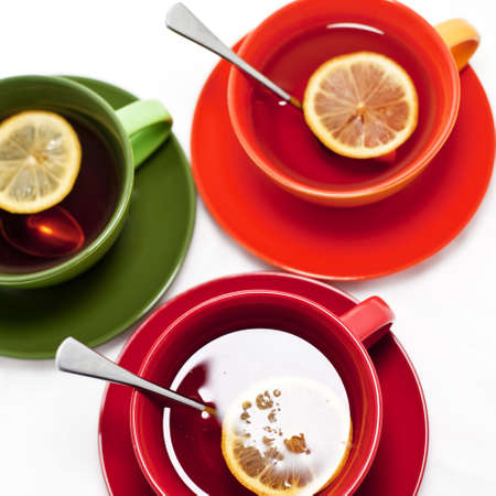 Three colored tea cups with tea and lemon Stock Photo - 14999571
