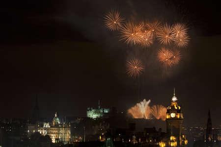 Edinburgh Cityscape with fireworks over The Castle and Balmoral Clock Tower photo