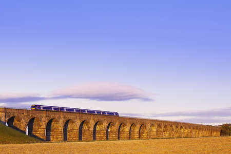 Old masonry arched viaduct carrying a train near Edinburgh, Scotland with sunset lighting photo