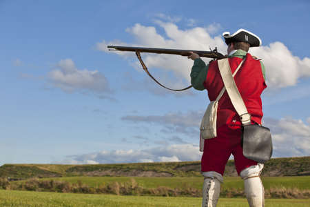 british army: Reenactor in 18th century British army infantry Redcoat uniform aiming his rifle    Stock Photo