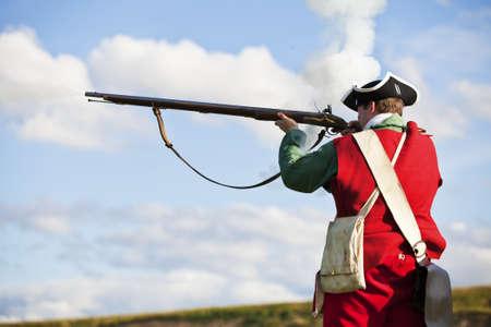 Reenactor in 18th century British army infantry Redcoat uniform aiming his rifle    Фото со стока