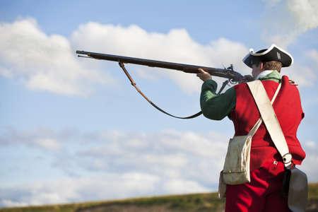 rifleman: Reenactor en el siglo 18 uniforme brit�nico Redcoat ej�rcito de infanter�a apuntando con su rifle Foto de archivo
