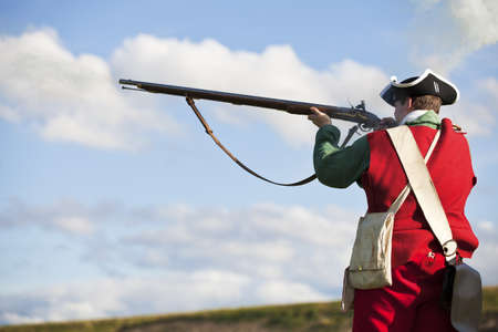 Reenactor in 18th century British army infantry Redcoat uniform aiming his rifle    Stock Photo