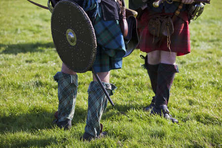scot: Legs of medieval Scottish warriors wearing tartan kilts. Selective focus on front man