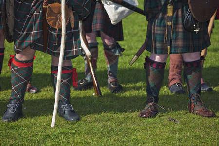 Legs of medieval Scottish warriors wearing tartan kilts. Selective focus on front men Фото со стока