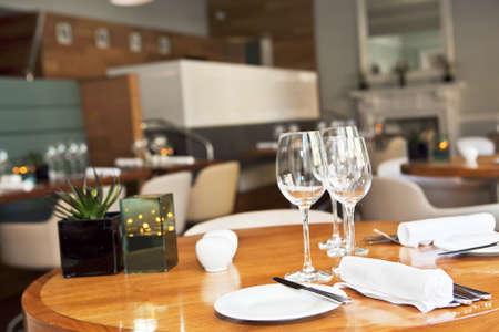 tavolo da pranzo: Piatto di pane con burro, coltello sul tavolo con sala da pranzo su sfondo. Messa a fuoco selettiva. Profondit� di campo Archivio Fotografico