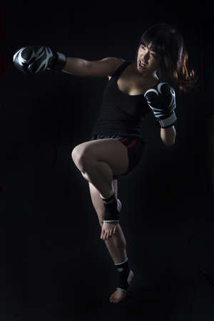Ung asiatisk kvinna Muay Thai fighter i defensiv position på svart bakgrund Stockfoto