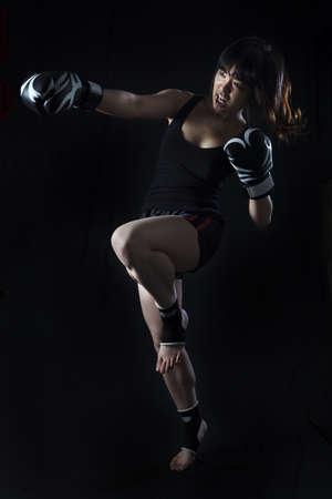 védekező: Young Asian Woman Muay Thai harcos védekező pozícióba fekete háttér