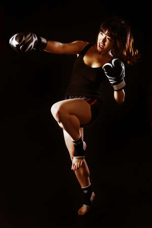 Young Asian Woman Muay Thai fighter in defensive position  On black background Imagens