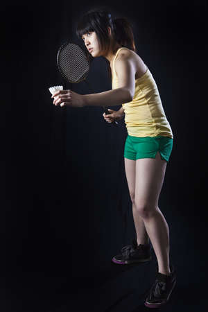 Asian woman with badminton racket isolated on black photo