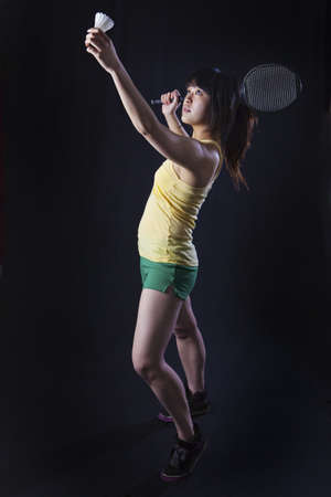 Asian woman with badminton racket isolated on black