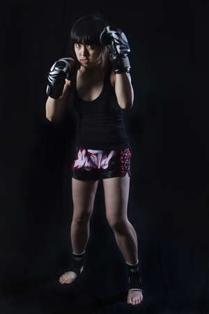 Young Asian Woman Muay Thai fighter in defensive position  On black background photo