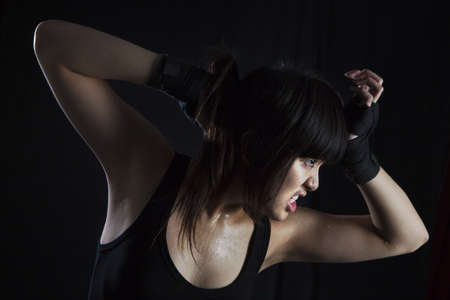 Perspiring Young Asian Woman working out and stretching muscles  On black background photo