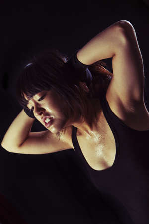perspiring: Perspiring Young Asian Woman working out and stretching muscles  On black background