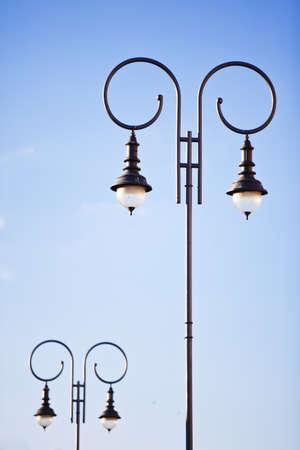 rhetorical: Oldfashioned decorative lamp post on the background of blue sky Stock Photo