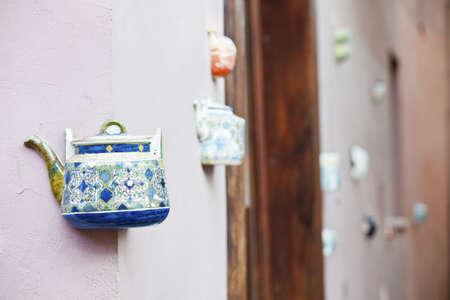 En tekanna satt i dekorativa fasader i butiken med keramik i Gamla stan i Vilnius, Litauen