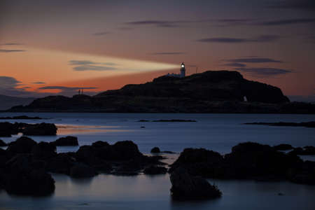 Lighthouse on Fidra island at astonishing sunset on vibrant sky background with light beam. Dirleton, Scotland photo