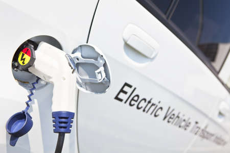 Electric charging noozle inserted into electrical vehicle's charging plug photo