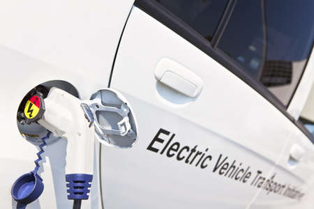 Electric charging noozle inserted into white electrical vehicle's charging plug. Concept photo