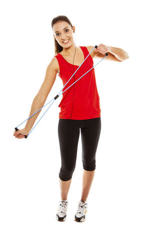 Young pretty fit woman exercising with elastic fitness band while listening music  Studio Isolated on white  High key photo