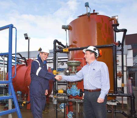 Två petrokemiska entreprenörer avsluta en affär framför en olje Refinary. Utomhus Stockfoto
