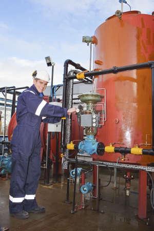 TPetrochemical entreprenör posingl framför ett oljeraffinaderi. Utomhus