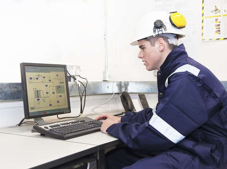 hardhat: Young engineer working with computer in office. Indoor Stock Photo